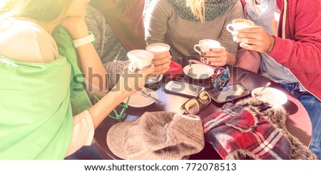 Group of best friends drinking coffee at bar cafe - Happy family moments gathering together around table on sunny winter day - Concept of people togetherness with natural sun backlight halo