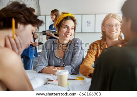 Group of best friends or university students hanging out at coffee shop, talking, having fun, spending nice time together, telling jokes and laughing, sitting at table with textbooks. Selective focus