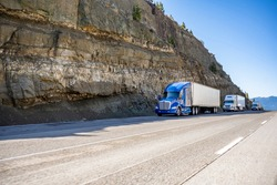 Group of big rigs semi trucks tractors transporting cargo in different semi trailers standing off road in a line near a stone cliff take a break at the pass on top of a mountain range in California