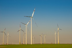 Group of big wind turbines to generate electrical power, green ecofriendly energy at blue sky with sunset warm colors in Europe. Concept of green sustainable energy production