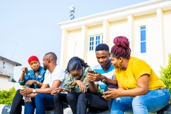 group of black african friends addicted by mobile smart phone. friends having fun outdoor using phone