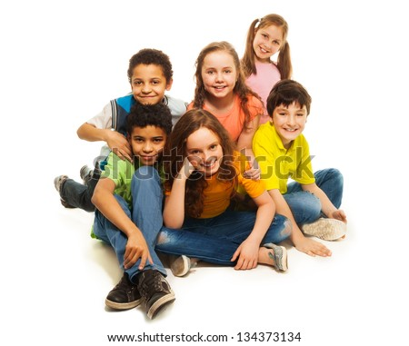 Group of black and Caucasian kids sitting happy together, smiling and laughing