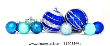 Group of blue Christmas baubles arranged as a border over white