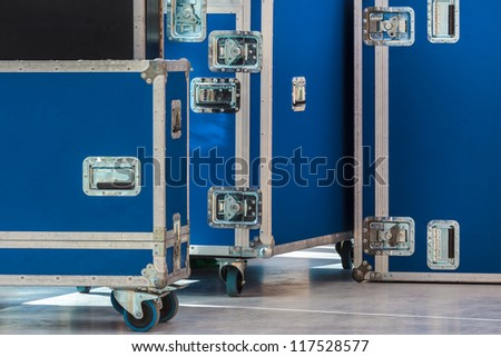 Group of blue flight cases on a grey floor