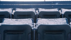 Group of blue, snowy bleachers with no one around during winter during bright day.