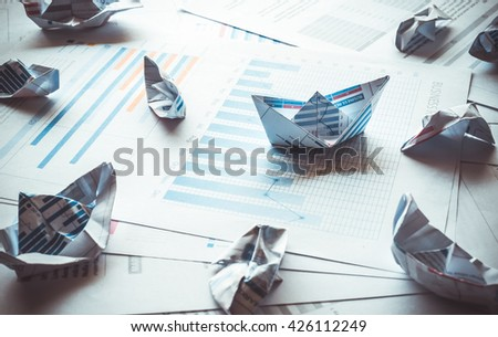 Group of boat made with paper graph in stormy of business.Only one boat can be success.Business success concept.