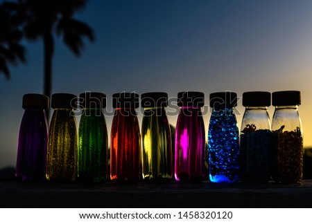 Group of bottles of calm anti stress, therapy to control stress and nerves of alternative education, filled with colored liquids to observe and relax.