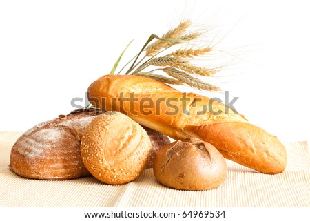 Group of bread and wheat spikes on a white background.