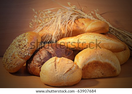 Group of bread and wheat spikes on wooden background. - stock photo