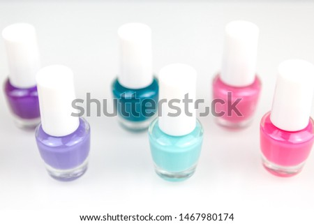 Group of bright multicolor nail polishes in a raw with reflection on a white table