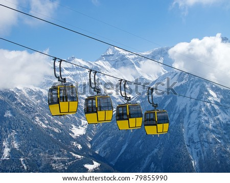 Group of bright yellow cable car cabins in swiss alps