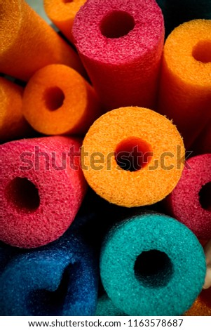 Group of brightly colored foam pool noodles clustered tightly together within the full frame #1163578687