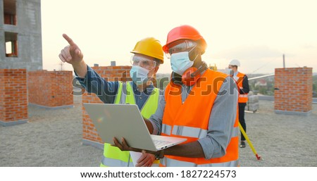 Group of builders in hardhat works on the building site. Two male builders  in medical face mask using laptop computer on construction site.