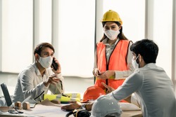 Group of building architect construction engineer have meeting and brainstorm together on table discussing about new project, teamwork talk with colleague. Members wear face mask prevent covid19 virus