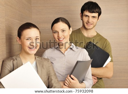 Group of business associates standing together against modern wooden wall at their office one woman holding laptop, man and other woman holding folder with papers and documents. Young entrepreneurs.