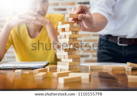 Group of business creative people building tower by wooden blocks, doing a plan for brainstrom business strategy, risk, future, teamwork concept