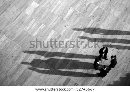 Group of business men gathered on a circle with long shadows.
