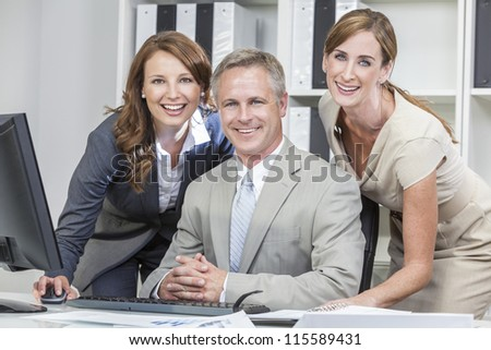 Group of business men & women, businessman and two businesswomen team, smiling using a computer in a modern office