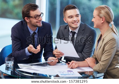 Group of business partners discussing ideas and documents in office - Shutterstock ID 157381295