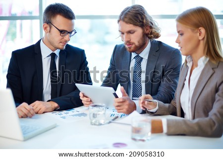 Group of business partners discussing project at meeting in office - Shutterstock ID 209058310