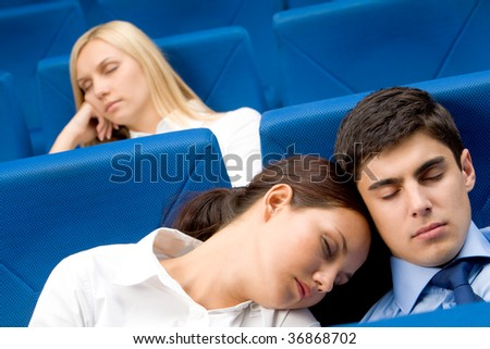 Group of business partners dozing in arm-chairs during presentation