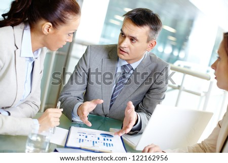 Group of business partners interacting at meeting in office
