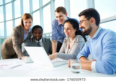 Group of business partners looking with smiles at laptop display at meeting #176050973