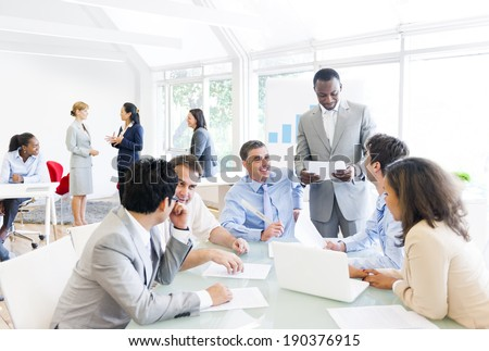 Group of business people around the conference table talking to one another. #190376915