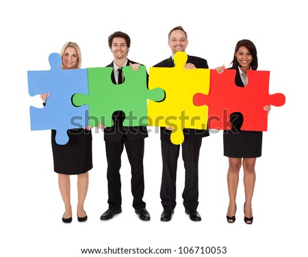 Group of business people assembling jigsaw puzzle. Isolated on white