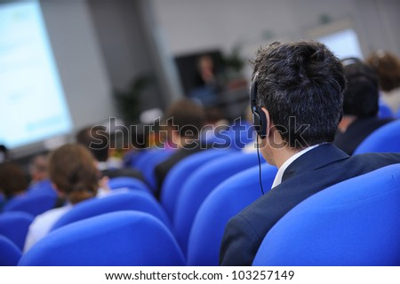 Group of business people attending press conference or presentation.