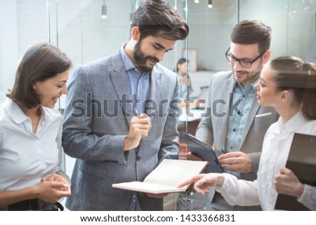 Group of business people discussing document on a meeting in the modern office.