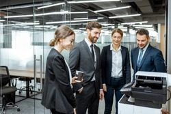 Group of business people hanging out together near the copier during a coffee break in the hallway of the big corporation