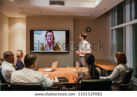 Group of business people having a late night video conference meeting. Sitting around a conference table talking and networking.