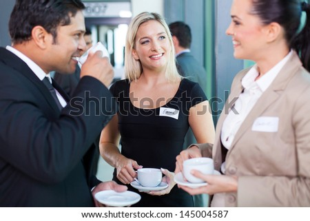 group of business people having coffee break during seminar