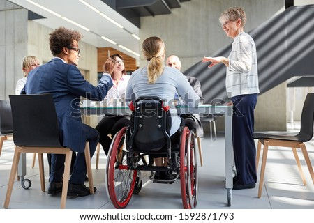 Group of business people in a meeting with colleague in a wheelchair for inclusion