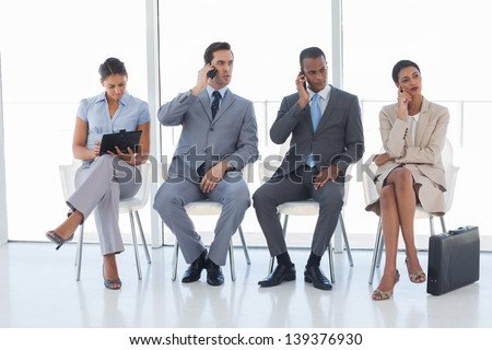 Group of business people in a waiting room using their phones and tablet