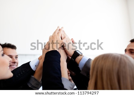 Group of business people joining hands together.