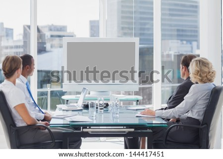 Group of business people looking at a screen during a video conference - stock photo