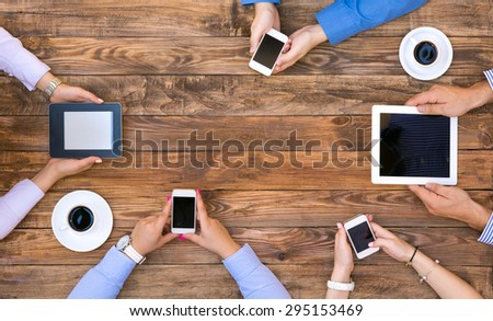 Group of Business People on Informal Meeting at natural wood Cafe Desk using variety of electronic gadgets connecting to internet and accessing data wireless two coffee mugs at corners