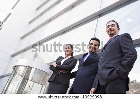 Group of business people outside modern office building