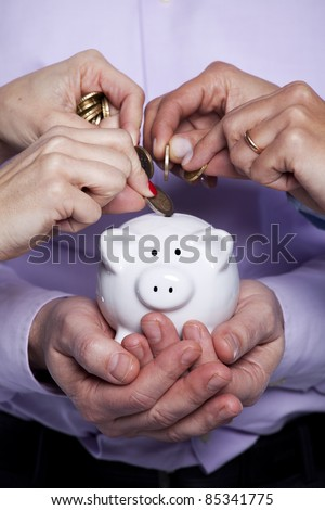 Group of business people saving money on the piggy bank