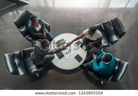 group of business people sitting and discussing statistics during a sit down meeting taking from above. Photo stock ©