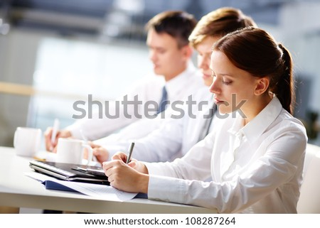 Group of business people taking notes at training
