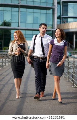 Group of business people walking not far from office building. Two women and their boss leaving for home after hard working day outdoors.