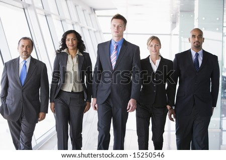 Group of business people walking through office towards camera