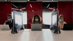Group of business people wear face mask and work in social distance with partitions in between as a part of new normal during coronavirus covid 19 in the meeting room at office workplace
