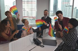 Group of business people with diverse genders (LGBT) celebrate LBGT freedom and support with LGBT flag in the meeting room at office workplace
