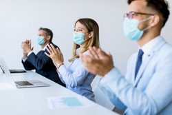 Group of business people with protection masks clapping hands after successful business meeting in the modern office