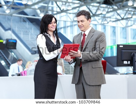Group of business people with tablet computer in the modern urban hall.