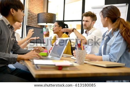Group of business persons having different age in creative business discussing work in the office